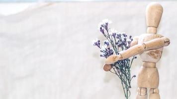 trä skyltdocka håller blommor foto