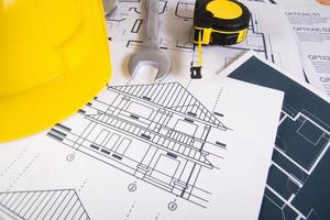 ingenjörsarbetsplats med ritningar, gradskiva och skyddshjälm foto