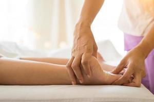 närbild av kvinnan som gör fotmassage på spa foto