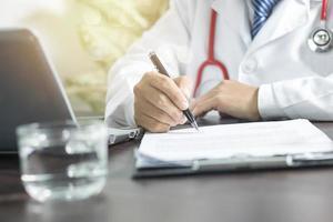 läkare som undertecknar pappersarbete foto