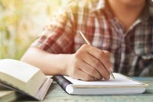 hand skriva i en anteckningsbok foto