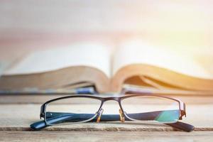 glasögon med öppen bok i bakgrunden foto