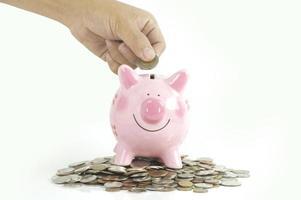 hand att sätta pengar i rosa spargris foto