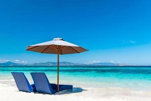 solstolar med paraply på sandstranden foto