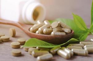 växtbaserade medicin kapslar på trä spole med blad på trä bord