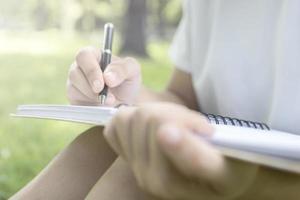 person som sitter och skriver i parken