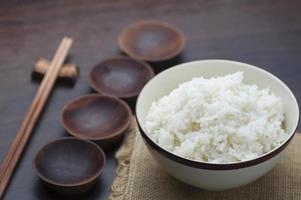 thailändskt vitt ris med pinnar på träbakgrund