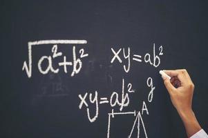 student skriver formeln med vit krita på tavlan foto
