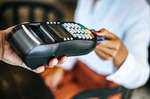 närbild av kvinna som betalar med kreditkort i kafé