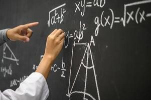 student med vit krita som visar formeln på tavlan foto