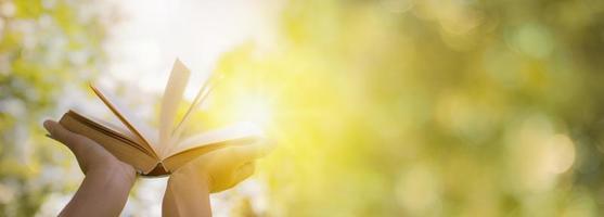 person som håller upp en bok i solen