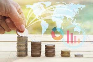 hand sätta pengar på hög med mynt koncept