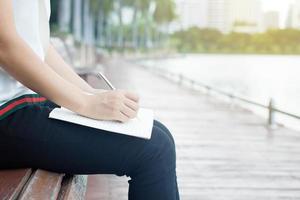 kvinnasammanträde och skriva på anteckningsboken i park foto