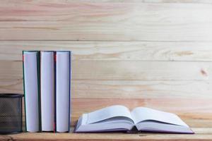 böcker på skrivbord och trä bakgrund foto