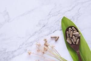 örtmedicin i kapslar på träsked med grönt blad på vit marmor foto