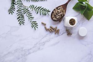 örtmedicin i kapslar på träsked med naturligt grönt blad på vit marmor foto