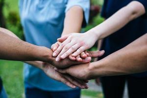närbild av ett team av studenter med händerna tillsammans foto