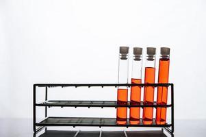 orange kemikalier i ett vetenskapligt glasrör ordnat på en hylla foto
