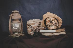 stilleben med skallarna i böcker, gamla lampor och vapen korsade foto