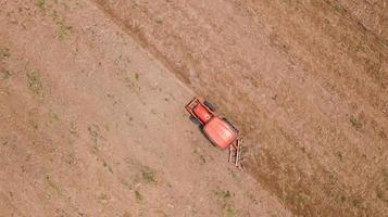 Flygfoto över en röd traktor i ett fält foto