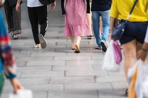 närbild på ben och skor som går på gatan i staden foto