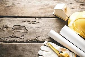 skyddande byggnadshjälm med ritningar och konstruktionsverktyg foto