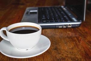 kaffe och bärbar dator på ett skrivbord foto