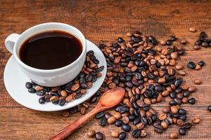 kopp kaffe med bönor på ett bord foto