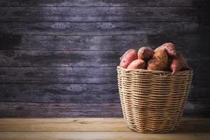 röda sötpotatis i korg foto