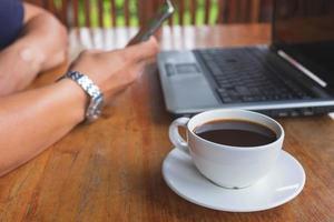 person som arbetar vid ett skrivbord med en kaffe foto