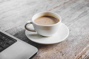 kopp kaffe och en bärbar dator foto