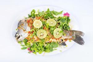ångad havsabborre i citron på maträtt som isoleras på vit bakgrund foto