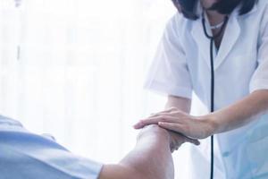 läkare som håller handen på patienten foto