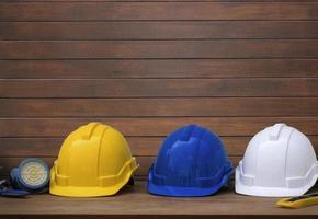 tre säkerhetshjälmar på gammal träbakgrund