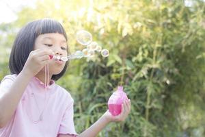söt ung flicka blåsa bubblor foto
