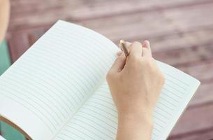 ung kvinna som skriver i anteckningsboken i park foto