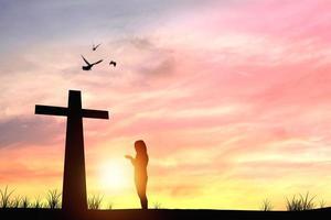silhuett av personen som ber vid ett kors vid solnedgången foto
