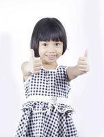 ung asiatisk tjej som håller upp två tummar