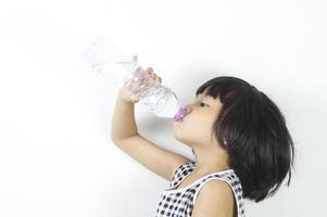 ung asiatisk tjej som dricker en flaska vatten foto