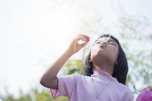 ung asiatisk unge som blåser bubblor i park foto