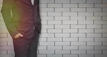 affärsman som står på tegelväggbakgrund med kopieringsutrymme
