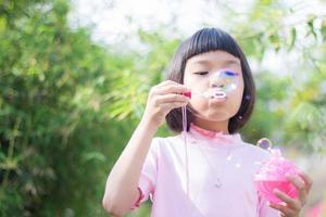 ung asiatisk tjej blåser bubblor foto