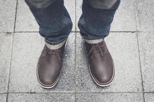 en man som bär blå jeans och läderstövlar foto