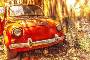 gammal rostig bil framför en smutsig vägg foto