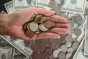 mynt i handen på dollarbankbakgrund