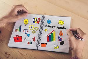 närbild av händer som skriver på papper med färgglada doodle-ikonen för företag