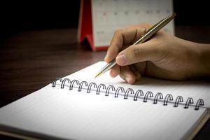 hand skriva på anteckningsboken i mörk ton foto