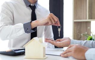 fastighetsmäklare som ger husnycklar till ny ägare foto