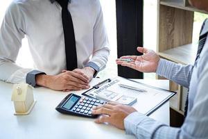 försäkringsblanketter med miniräknare, kontanter och nycklar foto