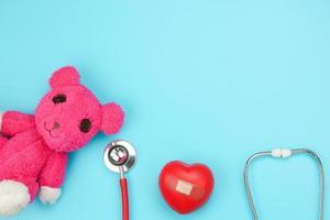 stetoskop och rosa björn på blå bakgrund foto